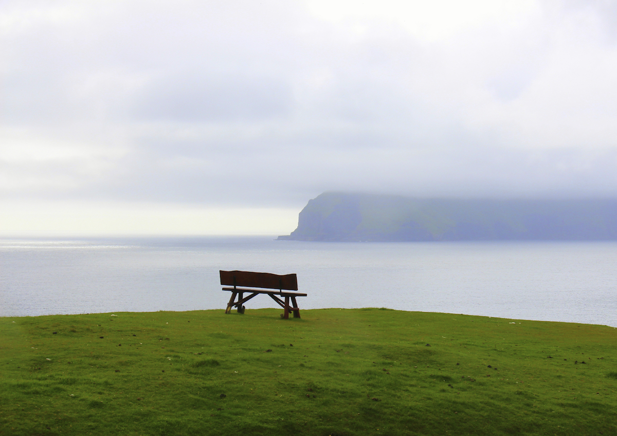 Bench on a hilltop with view to mountains on cloudy day